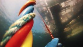 De duiker die van standpuntscooba colorfull kabels trekken om water aan oppervlakte weg te gaan stock video