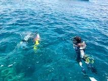 De duikers in zwarte duik maken kostuums met glanzende de bussenvlotter van het metaalaluminium waterdicht, duiken in het blauwe  royalty-vrije stock foto's