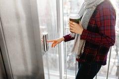 De duim drukt de Liftknoop, een hand die voor de knoop bereiken, het meisje die op Lift, drukknopbegin, het meisje wachten stock foto