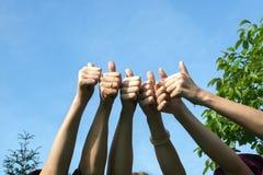 De duimen omhoog, vrienden heffen hun handen op en tonen hun duimen als a Stock Afbeeldingen