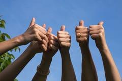 De duimen omhoog, vrienden heffen hun handen op en tonen hun duimen als a Stock Foto's