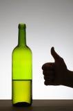 De duimen ondertekenen omhoog en een fles wijn Stock Fotografie