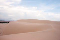 De duinen van het woestijnlandschap in de middag met blauwe hemel witte wolken royalty-vrije stock afbeeldingen