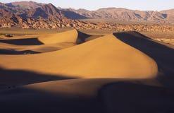 De duinen van het zand bij zonsondergang Stock Foto's