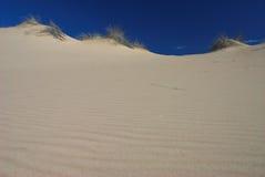 De duinen van het zand en blauwe hemel Stock Afbeelding