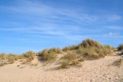 De duinen van het zand en een blauw. Stock Afbeeldingen