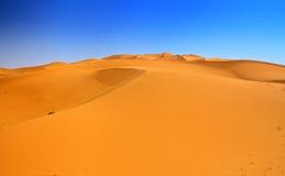 De duinen van het zand en wolkenloze blauwe hemel Stock Afbeelding