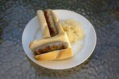 De Duitse die worsten riepen braadworsten in baguette met mosterd, ui worden geroosterd en legden zuurkool op witte plaat in Bosn royalty-vrije stock afbeeldingen