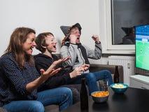 De Duitse familie let op het voetbal van de voetbalwereldbeker op TV stock foto's