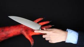 De duivel geeft een mes aan een mens stock footage