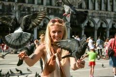 De duiven van de meisjesholding in Piazza San Marco Venice Italy De duiven wedijverden eens katten als traditionele, als officieu royalty-vrije stock afbeeldingen
