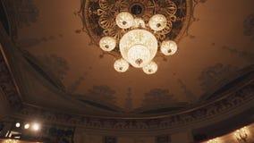 De dure gouden kroonluchter verschijnt van achter donker gordijn in concertzaal stock videobeelden