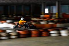 De dynamische karting concurrentie bij snelheid met onscherpe motie op een uitgeruste renbaan stock afbeeldingen