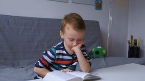 De e-book van de jongenslezing stock videobeelden