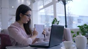 De e-lerende technologie, meisje het communiceren online op laptop apparaat en toont blocnote met nota's zittend bij lijst in kof stock footage