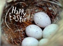 De echte kleine eieren in een stro nestelen het concept Pasen Inschrijving Gelukkige Pasen Selectieve nadruk Stock Foto