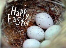 De echte kleine eieren in een stro nestelen het concept Pasen Inschrijving Gelukkige Pasen Selectieve nadruk Royalty-vrije Stock Afbeelding
