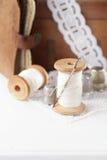 De echte oude loopvlakken van spoelenlepels met naald en vingerhoedje op witte wo Royalty-vrije Stock Afbeeldingen