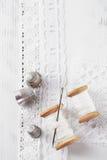 De echte oude loopvlakken van spoelenlepels met naald en vingerhoedje op witte wo Stock Afbeelding