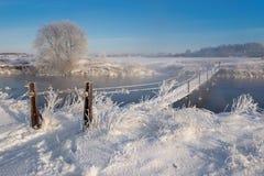 De echte Russische winter De winterlandschap met Sleep over de Gevaarlijke Landelijke Hangbrug over de Sneeuw Mistige Rivier Stock Afbeeldingen
