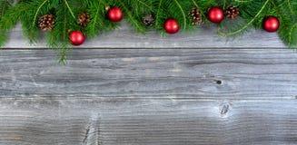 De echte takken van de Kerstmisspar en Rode ornamenten op doorstaan Royalty-vrije Stock Foto