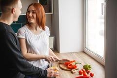 De echtgenoot bevindt zich in de keuken naast zijn vrouw wanneer zij kookt De vrouw kookt en glimlacht bij haar echtgenoot royalty-vrije stock fotografie