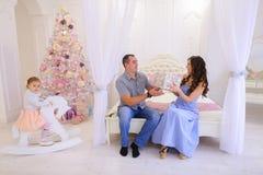 De echtgenoot en de vrouw geven elkaar Kerstmisgiften in heldere spaci Stock Foto's