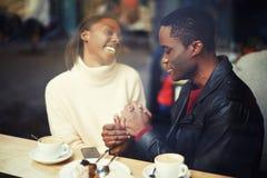 De echtgenoot en de vrouw zitten met de handen van een koffieholding Royalty-vrije Stock Afbeeldingen