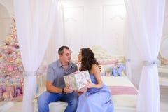 De echtgenoot en de vrouw geven elkaar Kerstmisgiften in heldere spaci Royalty-vrije Stock Afbeeldingen