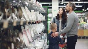 De echtgenoot en de vrouw kiezen platen in werktuigenafdeling in supermarkt, helpt hun kleine zoon hen buying stock videobeelden
