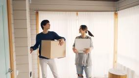 De echtgenoot en de vrouw komen binnen nieuw huis en brengende dozen met dingen na verhuizing, rond kijkend, het glimlachen stock video