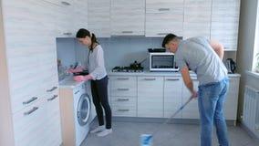 De echtgenoot en de vrouw maken samen in de keuken schoon De mens wast de vloer met een zwabber en de vrouw veegt het meubilair a stock video