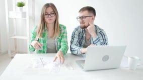 De echtgenoot en de vrouw tellen aankopen en rekeningen in de afgelopen maand en registreren de resultaten in hun huisboekhouding stock video