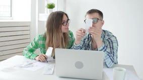 De echtgenoot en de vrouw tellen aankopen en rekeningen in de afgelopen maand en registreren de resultaten in hun huisboekhouding stock footage