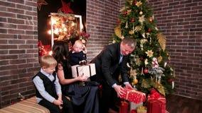 De echtgenoot geeft giften aan zijn vrouw en kinderen, een Kerstmispartij in de familie, vadermoeder en baby dichtbij Kerstmis stock videobeelden