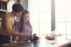 De echtgenoot giet koffie voor zijn vrouw in keuken stock foto's