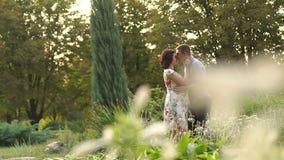De echtgenoot kust teder zwangere vrouw in een park stock footage