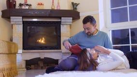 De echtgenoot las het boek aan zijn vrouw, het gelukkige echtpaar ontspannen dichtbij open haard stock videobeelden