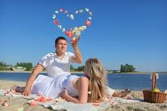 De echtgenoot maakt hart van roze bloemblaadje stock foto