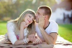 De echtgenoot met de zwangere vrouw ligt op een gras stock foto's