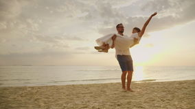 De echtgenoot omcirkelt zijn vrouw in zijn wapens Tegen de achtergrond van het overzees en de zonsondergang Gelukkige wittebroods stock footage