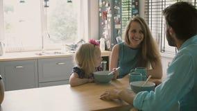 De echtgenoot spreekt aan zijn glimlachende vrouw terwijl hun dochter ontbijt Langzame motie heeft stock videobeelden