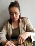 de economische groei, jonge vrouw die Mexicaanse muntstukken van tien peso's tellen stock afbeelding