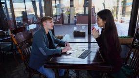 De econoom en de ingenieur kiezen schotels in comfortabel koffiehuis stock videobeelden