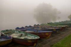 De een aantal geparkeerde boten tegen het meer in mist Stock Afbeelding
