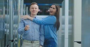 De een jonge mensendansen in een elektronikaopslag en bekijkt de camera, springt een vrouw en koestert en hem die uit glimlachen  stock videobeelden