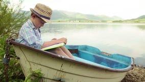 De een jongenszetels in een houten boot legden bij de bank vast en leest een boek stock videobeelden