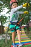 De een weinig gelukkige en glimlachende rotsklimmer bindt een knoop op een kabel Een persoon treft voor het stijgen voorbereiding stock foto