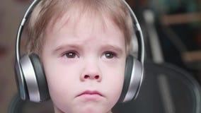 De een weinig grappige jongen zit als voorzitter en luistert aan muziek door hoofdtelefoons Dichte omhooggaand van het gezicht stock videobeelden