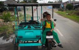 De een weinig Indonesische jongen berijdt een tuk-tuk en lacht merrily stock foto
